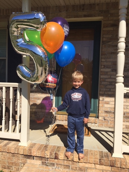 little boy holding birthday balloons