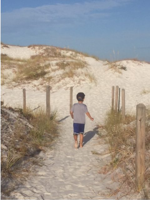 little boy walking up sand dunes