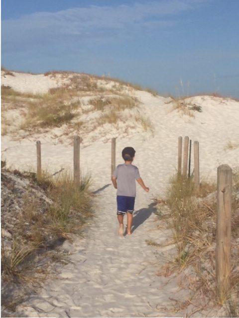 little boy walking up sand dunes