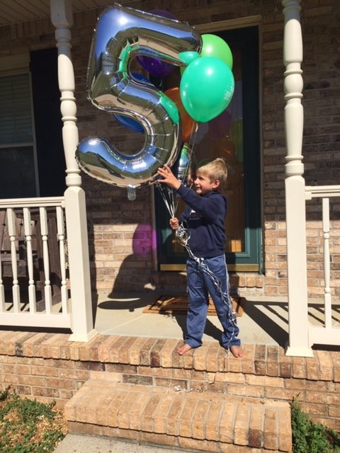 little boy with birthday balloons