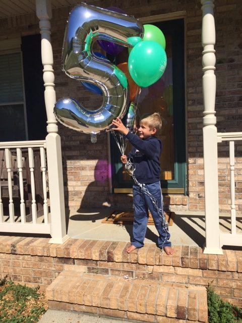 little boy with birthday balloons