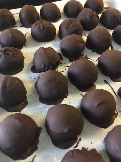 baking sheet full of chocolate covered peanut butter balls