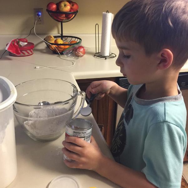 little boy measuring baking powder