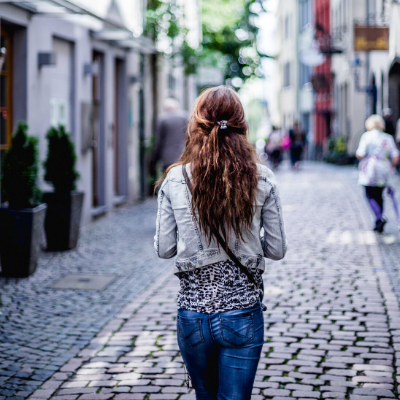 woman walking down cobblestone streets