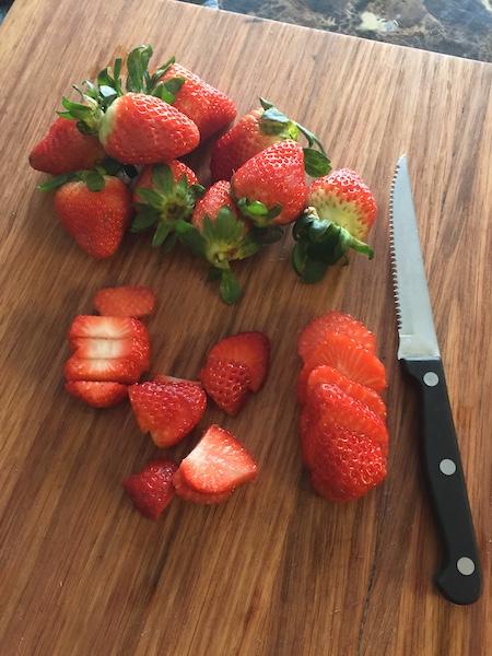 sliced strawberries on cutting board