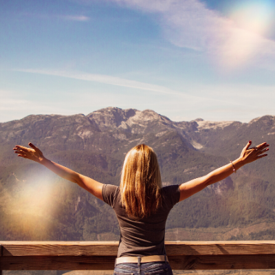 woman with outstretched arms looking at mountains