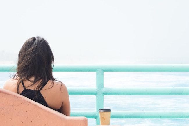 woman sitting overlooking the ocean