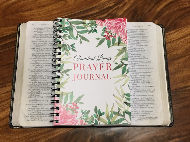 abundant living prayer journal on top of bible