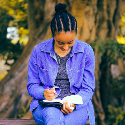 black woman sitting outside reading a book