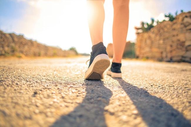 feet walking on a gravel path