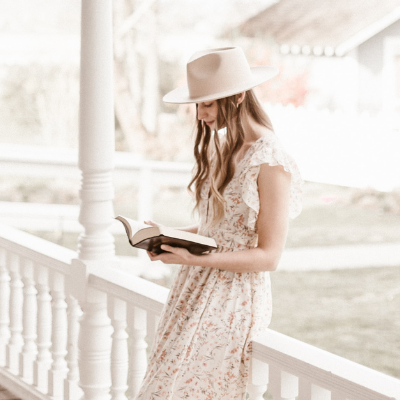 woman leaning on porch railing reading her bible